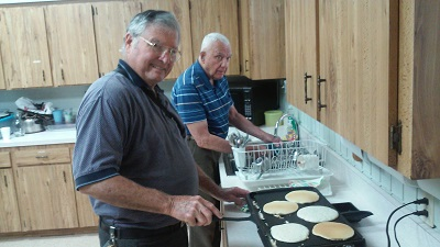 Stan cooking pancakes and Jack washing dishes.